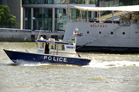 Police Boat on the Thames River, passing HMS Belfast